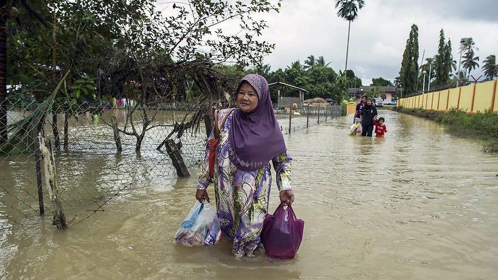 a_woman_walks_through_the_floodwaters_ne